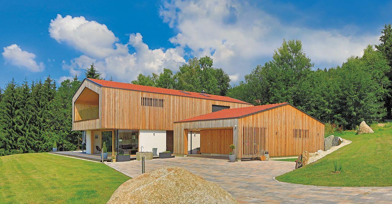 Modernes Massivholzhaus mit teilverputzter Fassade