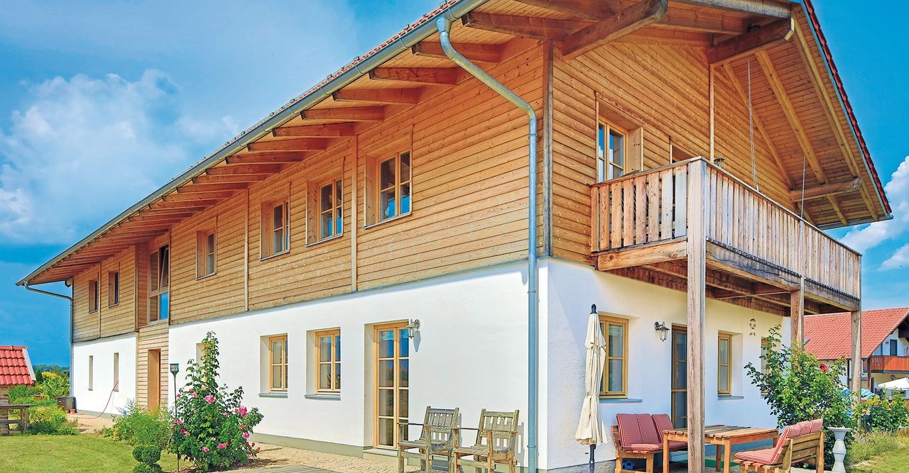 Großes Massivholzhaus mit Balkon und teilverputzter Fassade